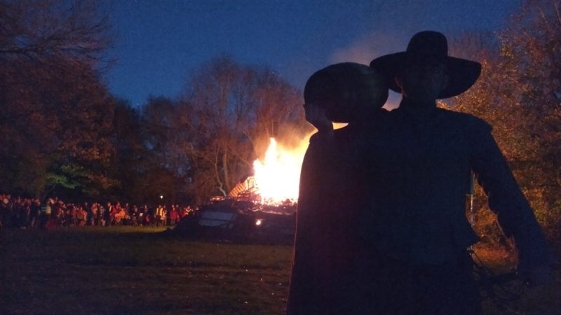 Guy Fawkes re-enactor in front of bonfire flames at Avoncroft Museum